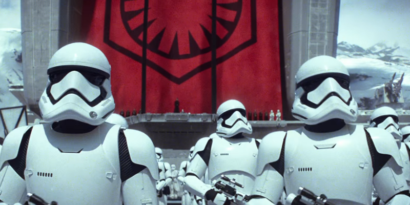 First Order stormtrooopers stand to attention in front of an enormous First Order flag.