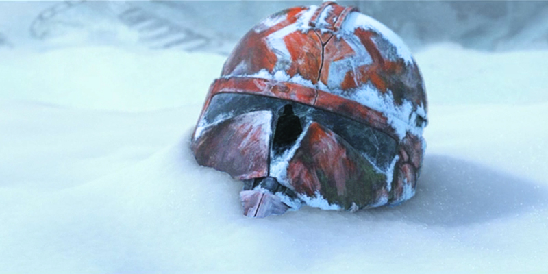 A clone helmet, painted in orange and white, lies cracked and abandoned in the snow, its visor reflecting the silhouette of Darth Vader